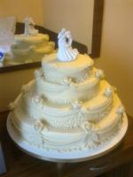 Natúr színű marcipánnal burkolt és díszített esküvői torta, nászpárral