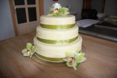 Zöld szalaggal és orchideával díszített esküvői torta